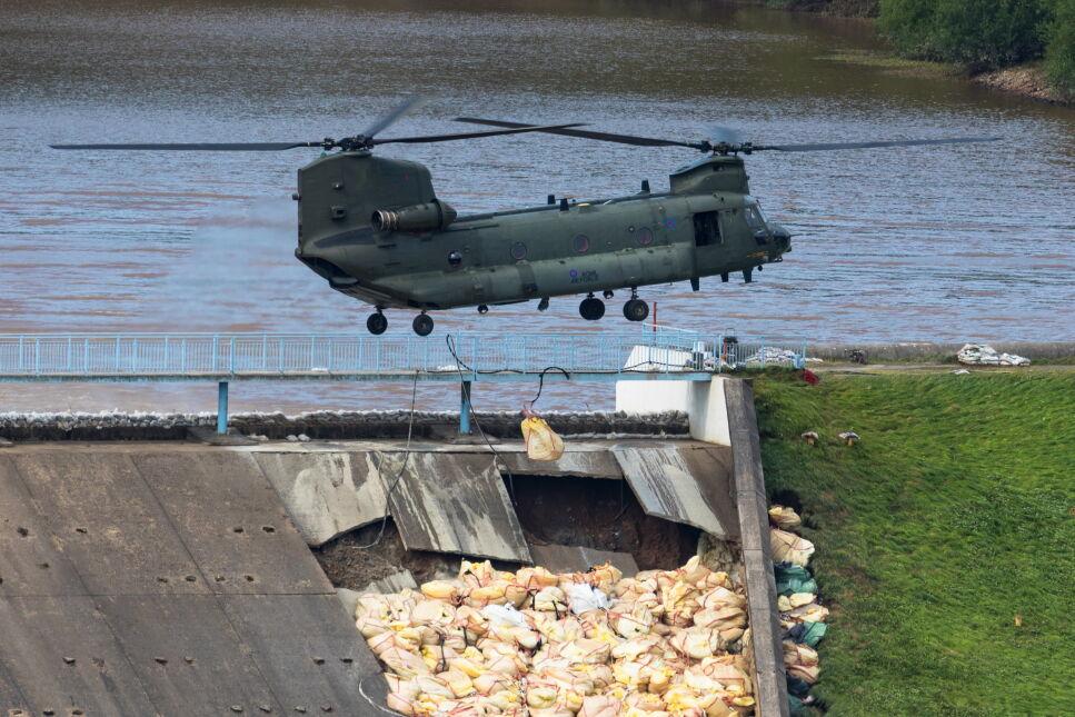 Helikopter Chinook przygotowuje się do zrzucenia worków z piaskiem na uszkodzoną tamę zbiornika Toddbrook w Whaley Bridge, Wielka Brytania