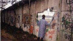 Mieszkanka Berlinu Wschodniego patrząca przez dziurę na Berlin Zachodni
