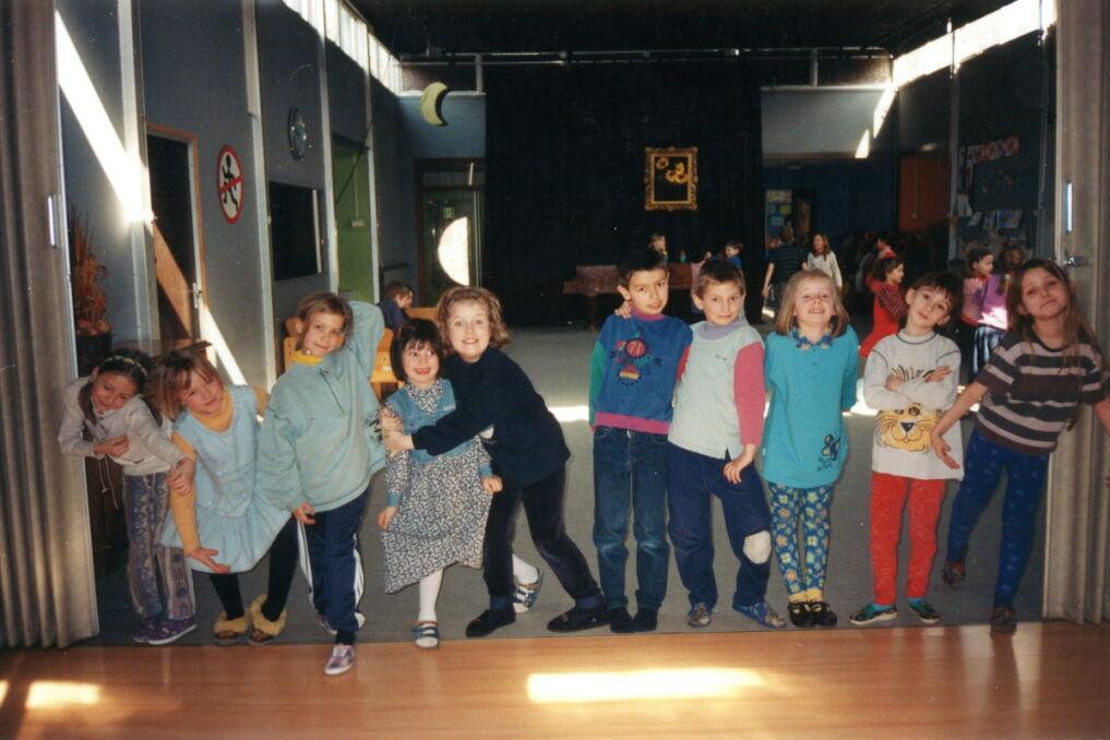 Dzieci stojące przy harmonijce oddzielającej hol młodszych klas od starszych