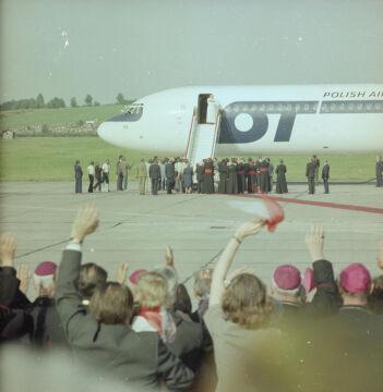 Papież Jana Paweł II żegna Polaków ze schodów samolotu Ił-62 M o numerze rejestracyjnym SP-LBE w barwach Polskich Linii Lotniczych LOT przed odlotem do Rzymu. Na płycie lotniska widoczni m.in. biskupi, księża, przedstawiciele władz. U dołu widoczni uczestnicy uroczystości, w tym biskupi, pozdrawiający papieża - 1983-06-23